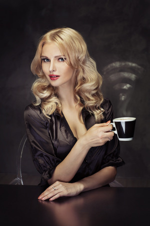 Beautiful lady holding the vaporous cup of coffee photo