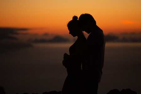 Silhouettes of the calm, young couple Imagens
