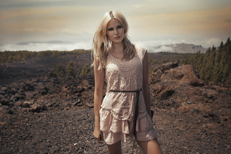Cheerful blond lady on the stone desert photo