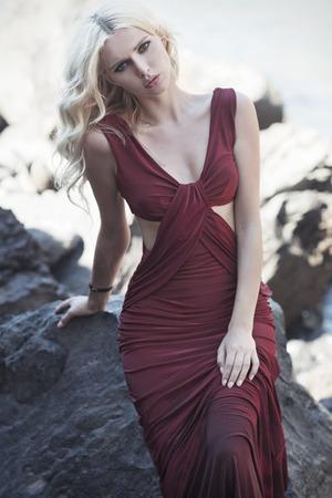 岩の上に座っている金髪のかわいい女性の肖像画