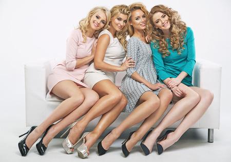 Attractive girlfriends sitting on white sofa