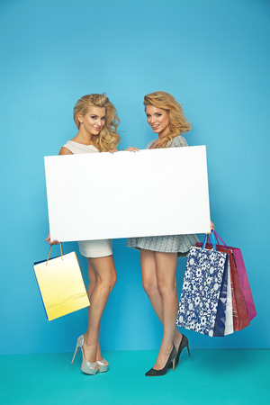 Blond ladies holding white board