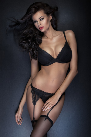 seductress: Brunette tawny lady wearing sensual, black underwear Stock Photo