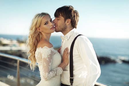 Handsome young groom kissing his lovely wife