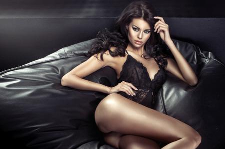 piernas con tacones: Mujer morena atractiva que miente en el sofá negro Foto de archivo