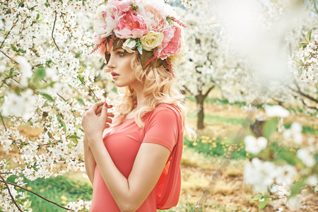 fragrant: Charming blond woman walking in the fragrant orchard