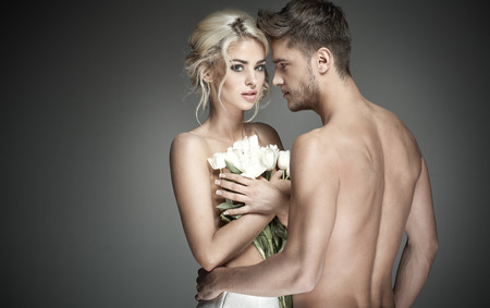 nude: Portrait of a handsome guy with blond womkan holding pearl roses