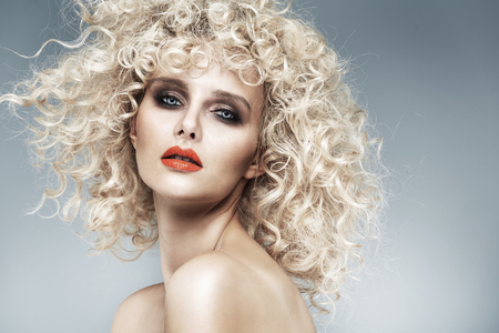 Schöne Blondine mit einem malerischen lockige Frisur