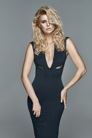 Bella donna bionda di fascino che indossa un abito nero