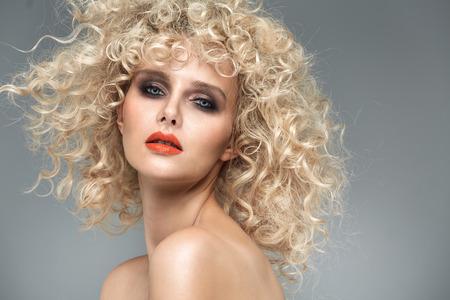 화려한 곱슬 머리 장식을 가진 아름다운 금발의 여인
