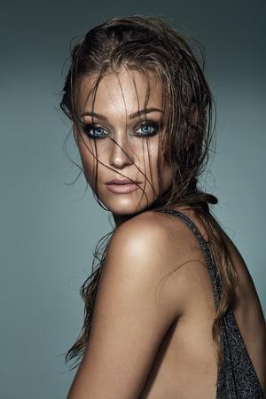wet: Retrato de una mujer atractiva de moda con el pelo mojado y los ojos magníficos