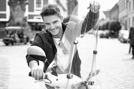 young male: Portrait of happy young guy riding a scooter