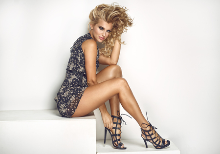 heel: Sexy blonde lady posing isolated in fashionable dress