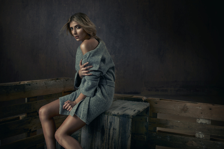 Fashion natural young lady sitting on a wooden chest Stock fotó