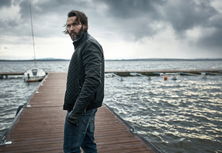 persona mayor: El hombre elegante y guapo descansando en el lago