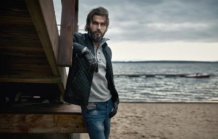 秋のビーチで休んで成熟したハンサムな男の肖像 写真素材