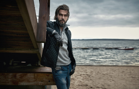 Portrait of a mature handsome man resting on the autumn beach