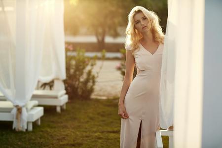Calm woman walking among white deckchairs Standard-Bild