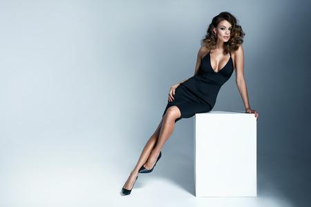 Foto van een sexy brunette vrouw draagt zwarte jurk