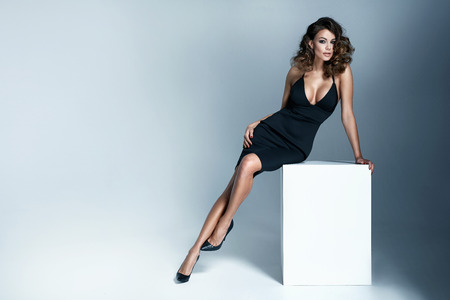 Photo of a sexy brunette woman wearing black gown Фото со стока