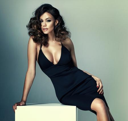 Foto van een schattige brunette vrouw die een zwarte jurk draagt Stockfoto