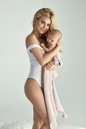 motherhood: Young, beautiful blond mom carrying a newborn baby