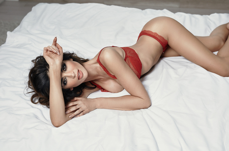 Photo of sexy brunette woman lying on the bed Stock Photo