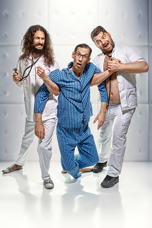 Portrait of funny doctors and lunatic in the madhouse