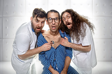 Two odd psychiatrists examining a funny lunatic
