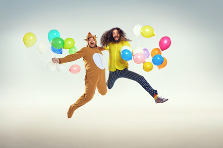 Picture presenting two funny men jumping and holding balloons