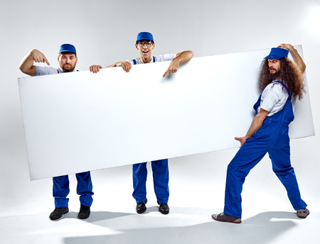 Conceptual picture of three crafstmen holding an empty, white board