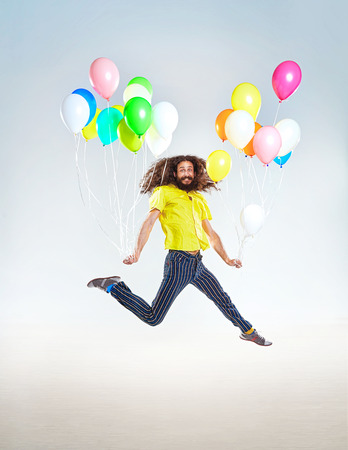 Conceptual portrait of a childish guy jumping with balloons Stockfoto