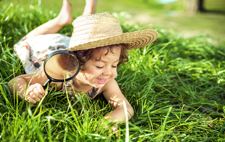 Cute little girl having fun with a magnifying glass Stock Photo