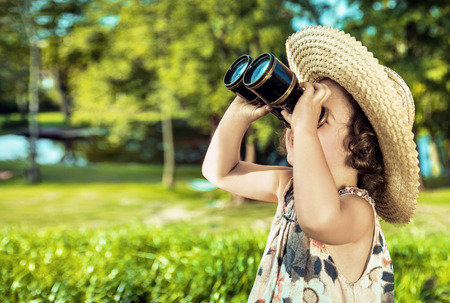 Happy little child looking around with a vintage binoculars Stock Photo