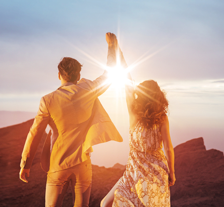 Ambitious, young couple looking at the sunset with a victorious gesture Reklamní fotografie