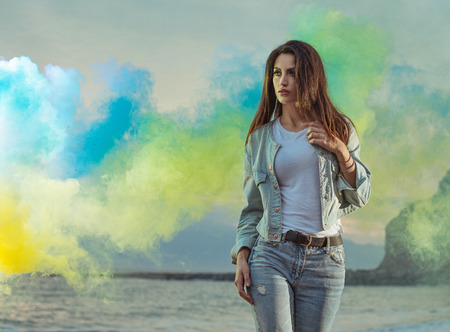 Beautiful brunette lady among colorful smoke Banco de Imagens