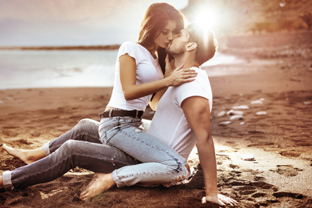 Fashion shot of an attractive couple kissing in the paradise