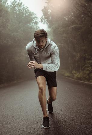 Closeup shot of a stretching muscular jogger