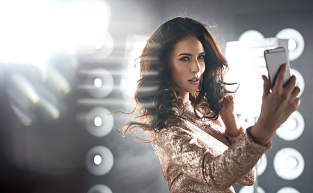 Portrait of a brunette, elegant woman taking a selfie