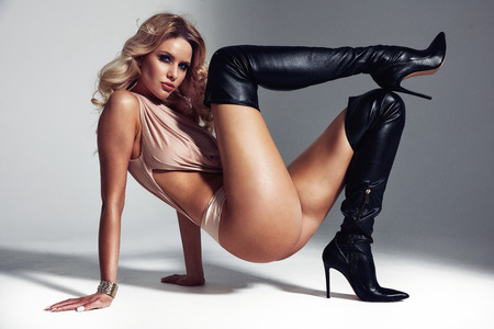 Art portrait of a sensual blond lady wearing black boots