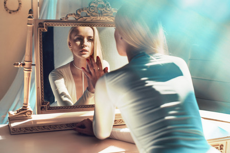 elegant blond woman looking at her mirror reflection