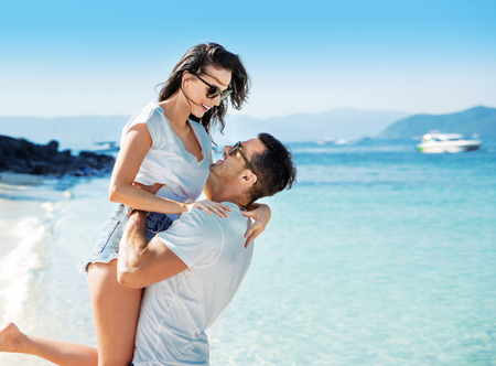 Young and cheerful couple relaxing on a tropical beach