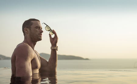Portrait of a muscualar, handsome man relaxing in a tropical, hot water