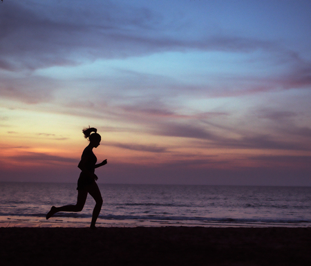 Young, athletic woman jogging on a beach during the susnet Stock Photo