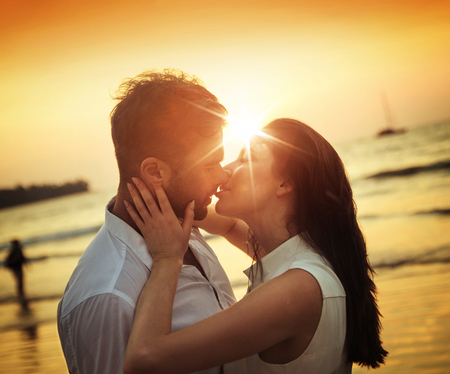 Young, romantic couple kissing on a hot, tropical beach Stock Photo