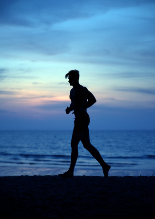 Muscular man jogging on the tropical beach - evening exercises