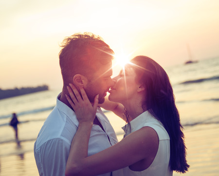 Young, romantic couple kissing on a hot, tropical beach 版權商用圖片