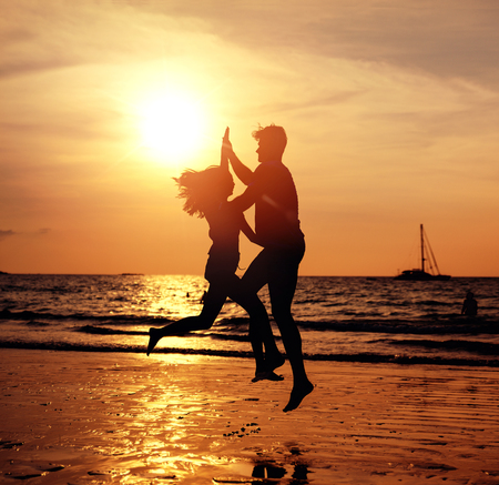Portrait of  young lovers on the tropical beach, posing on sunset background