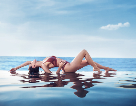 Sensual, young woman relaxing in a hot, tropical pool