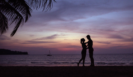Romantic portrait of a young couple hugging on a tropical brach - sunset circumstance